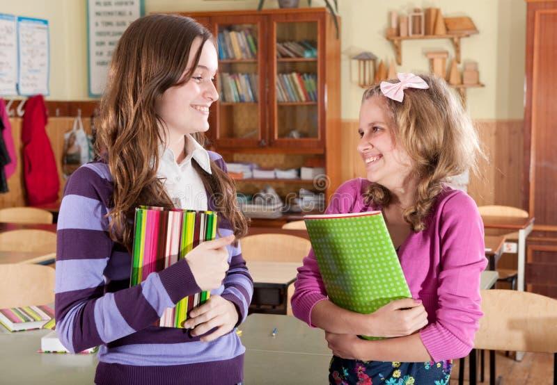 Två kvinnligklasskompisar som ler i calssroom royaltyfri foto