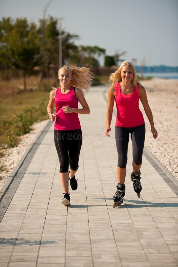 Två kvinnor övar på strandspring och rollerblade som nära åker skridskor arkivfoton