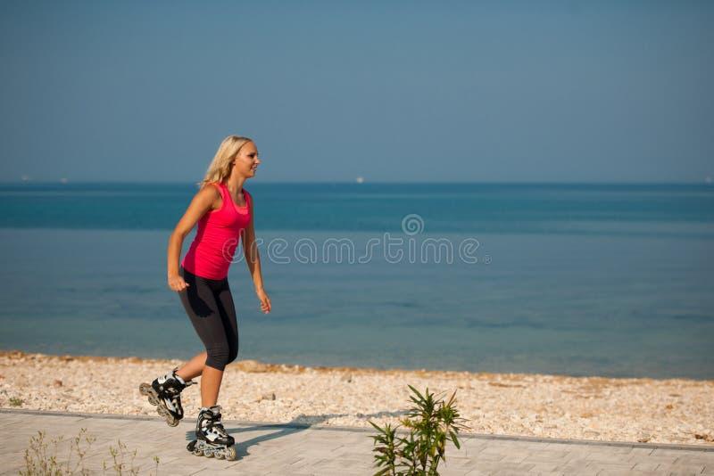 Två kvinnor övar på strandspring och rollerblade som nära åker skridskor arkivbilder