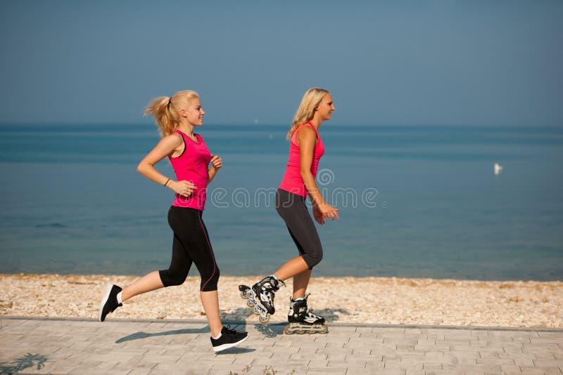 Två kvinnor övar på strandspring och rollerblade som nära åker skridskor arkivbild