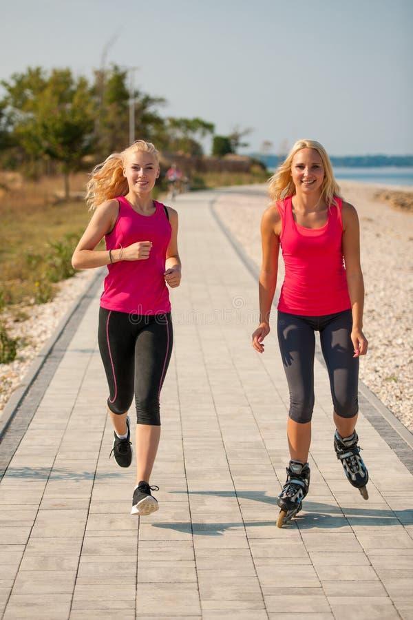 Två kvinnor övar på strandspring och rollerblade som nära åker skridskor royaltyfria foton
