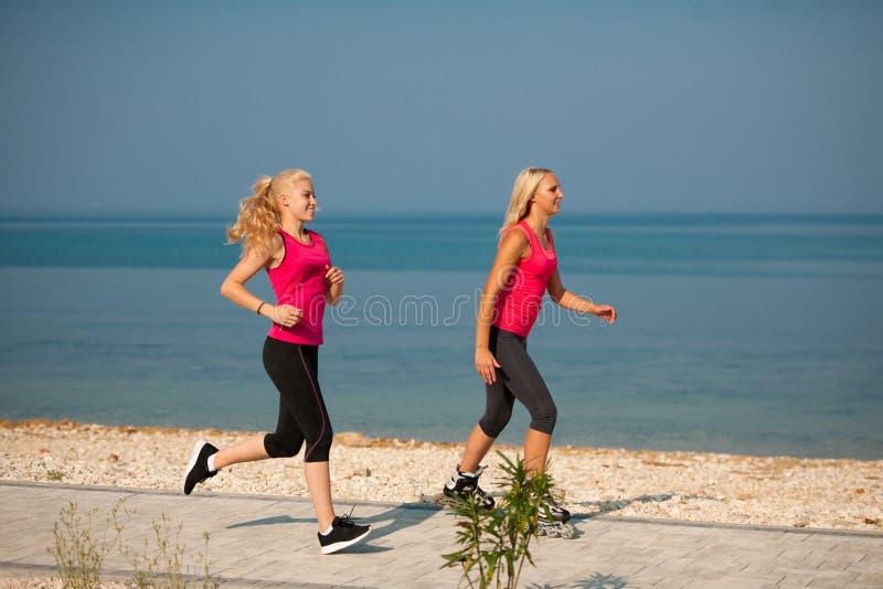 Två kvinnor övar på strandspring och rollerblade som nära åker skridskor royaltyfri fotografi