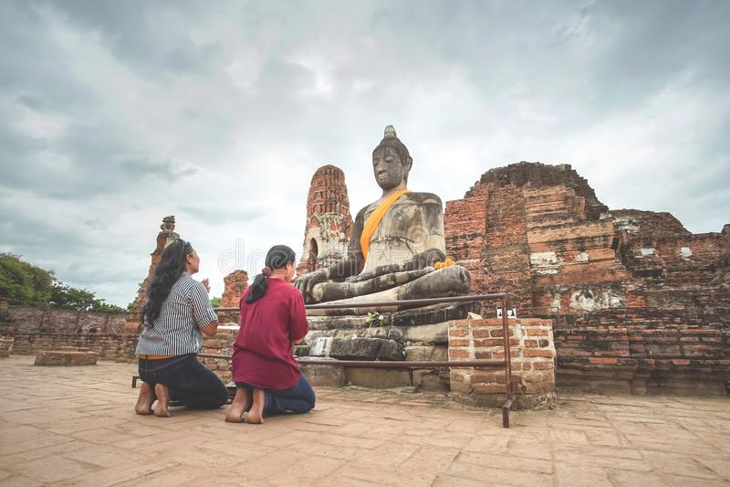Två kvinnor ber till Buddhastatyn i Wat Mahathat, Ayut arkivbilder