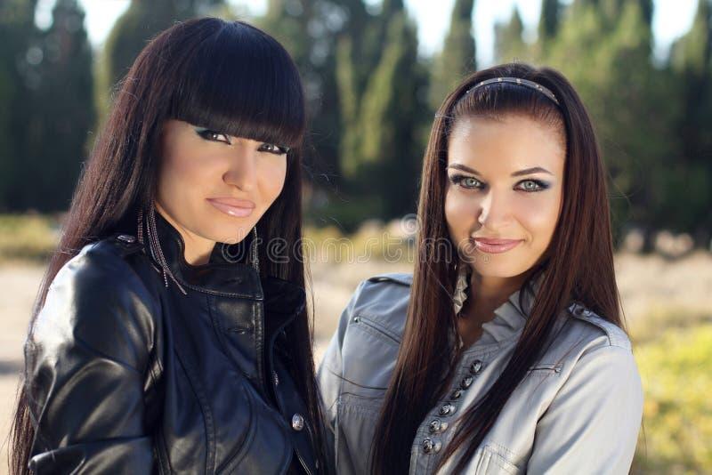 Två kvinnor. Closeup av härliga unga flickor, utomhus stående royaltyfri fotografi