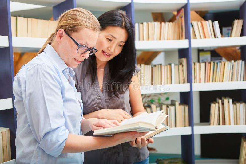 Två kvinnor går igenom en bok tillsammans royaltyfri bild