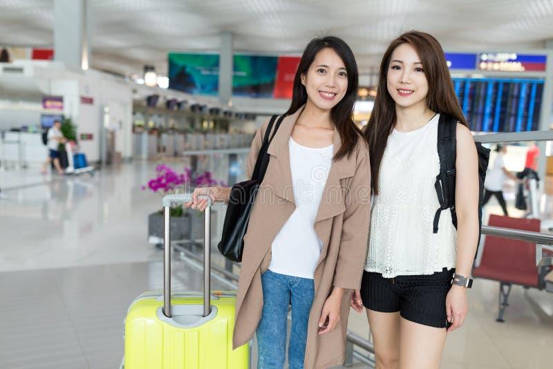 Två kvinnor går loppet tillsammans i Hong Kong den internationella flygplatsen fotografering för bildbyråer
