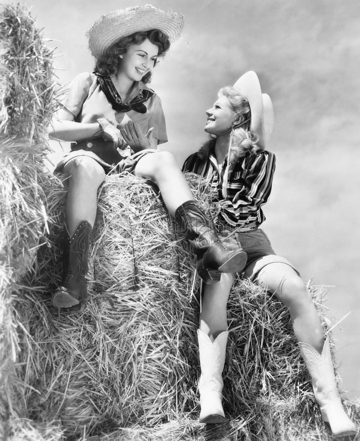 Två kvinnor i cowboyhattar som sitter på en höstack (alla visade personer inte är längre uppehälle, och inget gods finns Leverant fotografering för bildbyråer