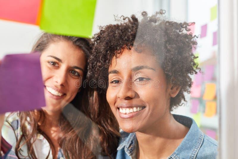 Två kvinnor i det mångkulturella start-up laget arkivbild
