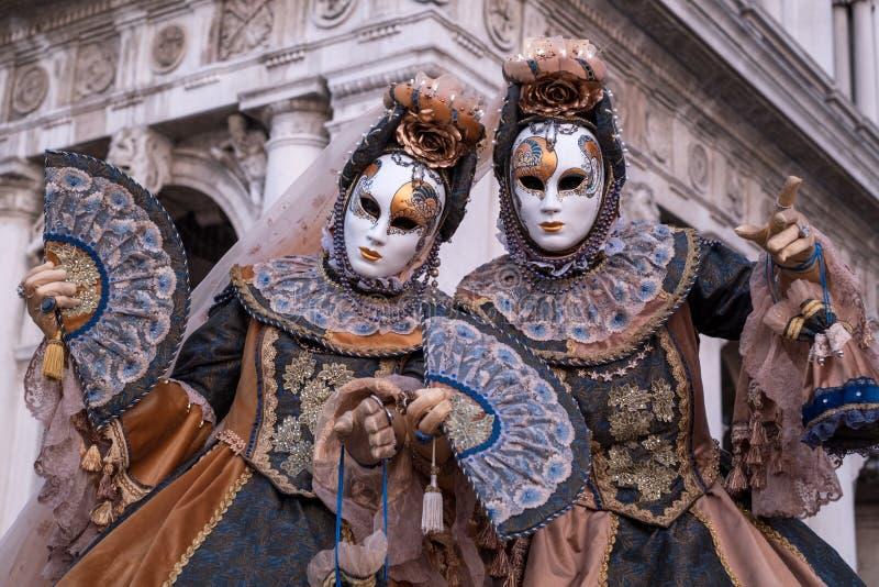 Två kvinnor i maskeringar och dräkten, med dekorerade fans som står av bågarna på St-fläckar, kvadrerar framme under den Venedig  royaltyfri bild