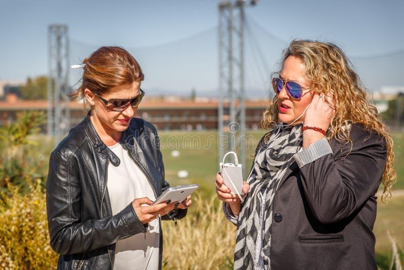 Två kvinnor i omslag pratar på gatan, medan ett av dem kontrollerar en minnestavla royaltyfri foto