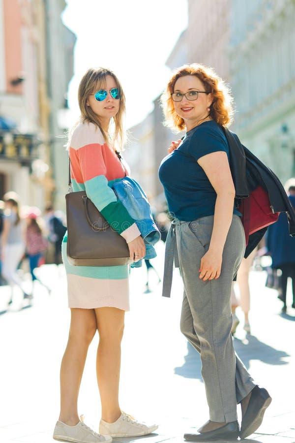 Två kvinnor i staden som pratar gå tillsammans centret royaltyfri bild