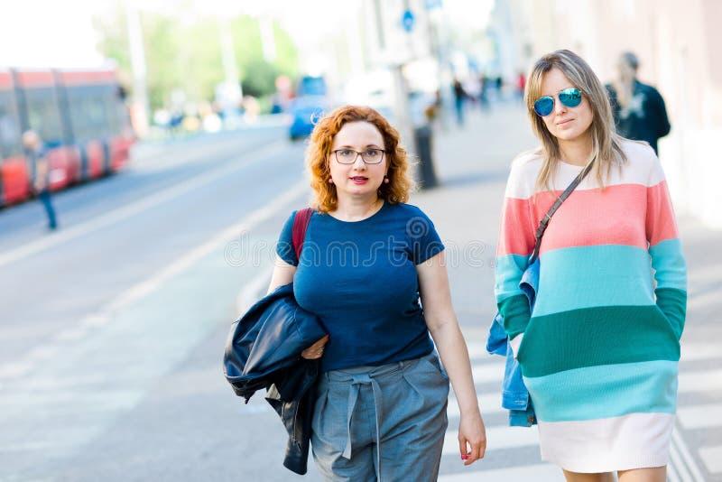 Två kvinnor i staden som tillsammans går royaltyfri bild