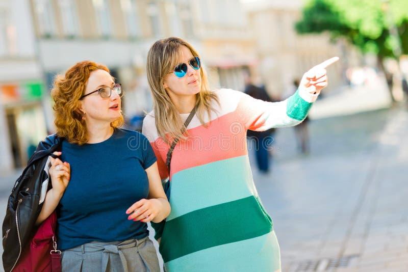 Två kvinnor i staden som tillsammans går - peka arkivfoton
