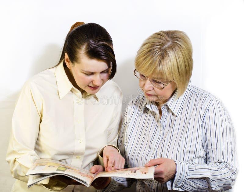 Två kvinnor läste en modetidskrift royaltyfria foton
