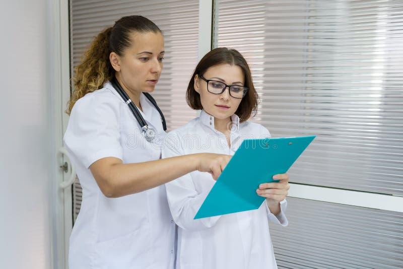 Två kvinnor manipulerar och vårdar samtal på sjukhuset på dörrbakgrunden arkivfoto