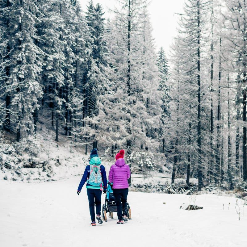 Två kvinnor med behandla som ett barn sittvagnen som tycker om moderskap i vinterskog fotografering för bildbyråer