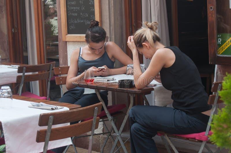 Två kvinnor med den smarta telefonen i restaurangterrass royaltyfri foto