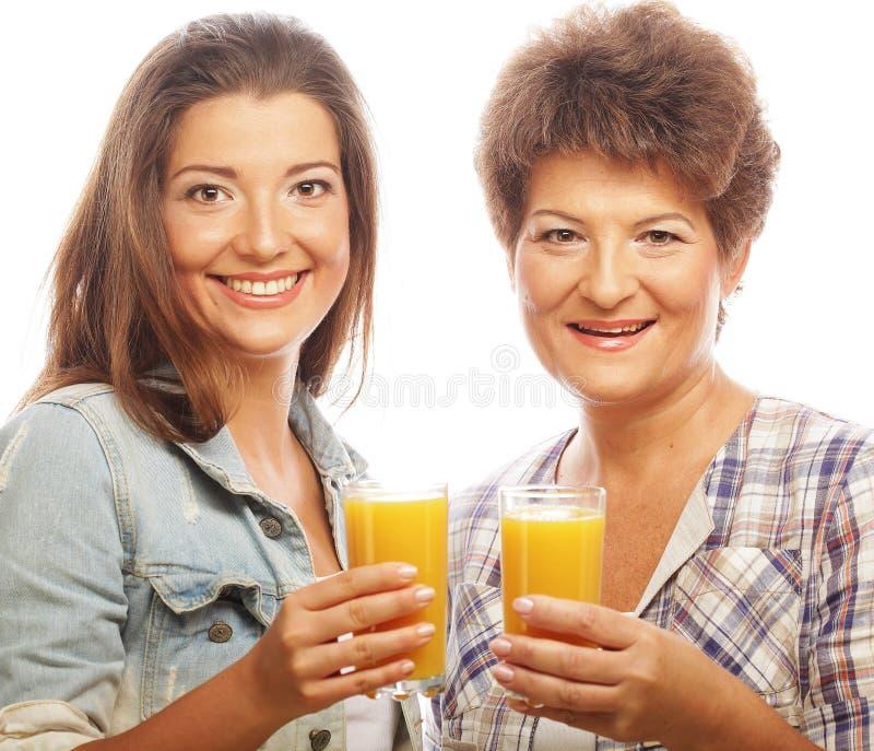 Två kvinnor med orange fruktsaft arkivbild