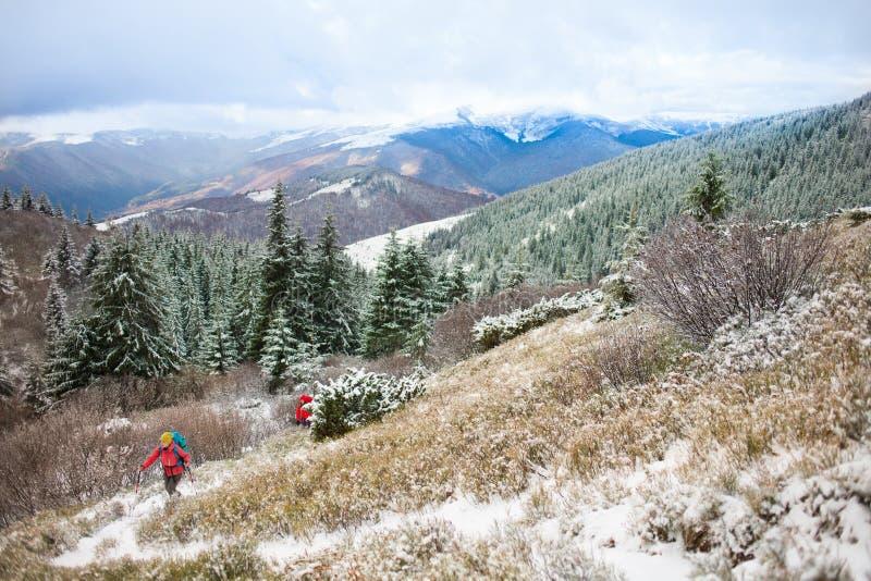 Två kvinnor med ryggsäckar i bergen i vinter arkivfoto