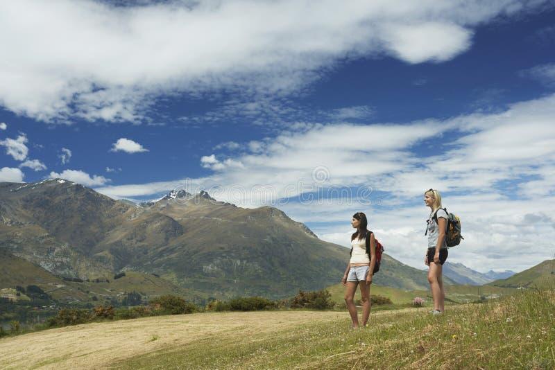 Två kvinnor med ryggsäckar på berglandskap royaltyfri foto