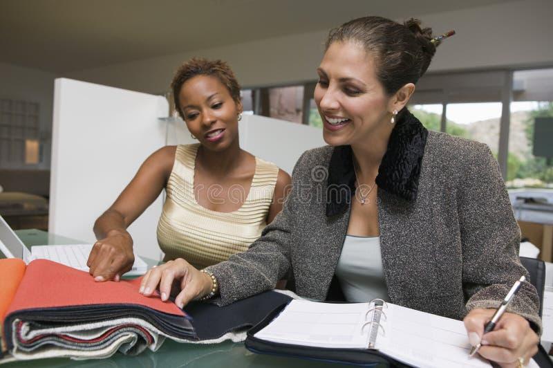 Två kvinnor med undersökande tygprovkartor för bärbar dator och för organisatör arkivbild