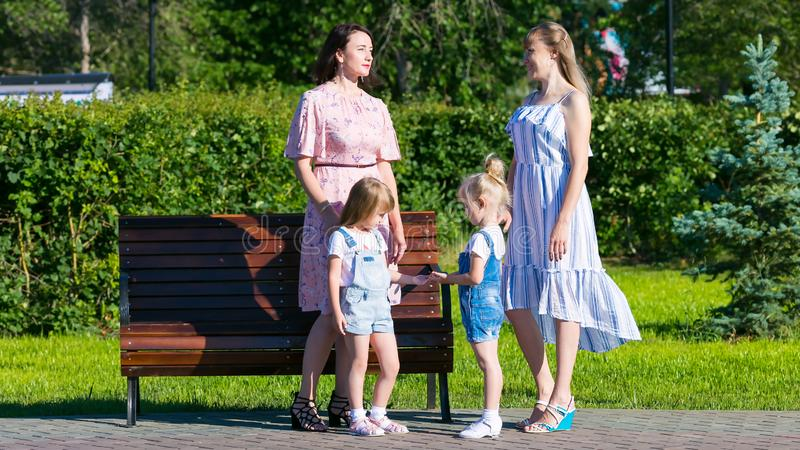 Två kvinnor med unga barn på gatan royaltyfri bild