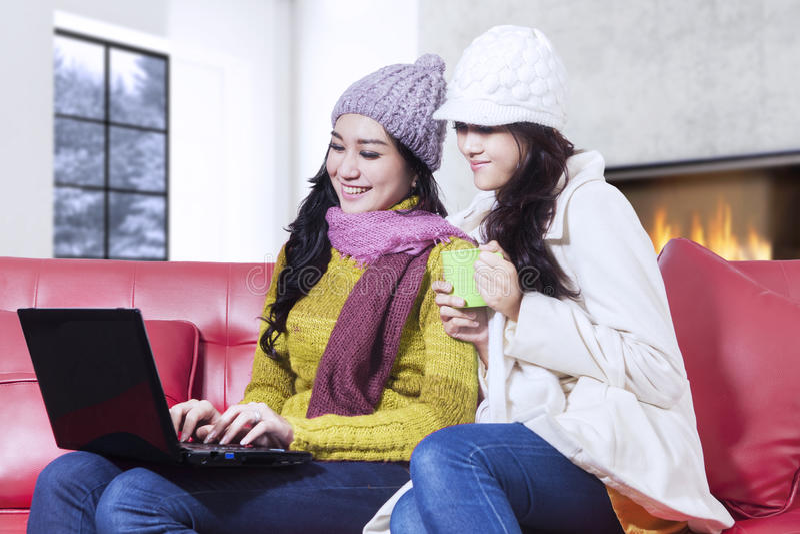 Två kvinnor med vinterkläder genom att använda bärbara datorn royaltyfri bild