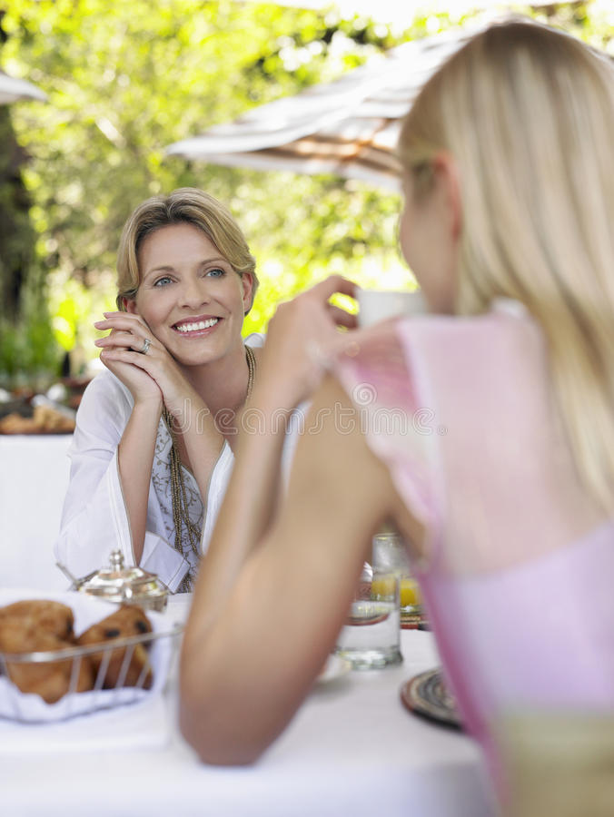 Två kvinnor på utomhus- prata för tabell arkivbilder