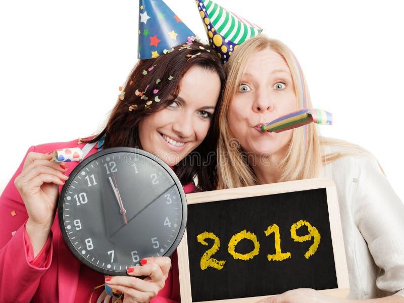 Två kvinnor rymmer den svart tavlan för det nya året 2019 - som isoleras på vit bakgrund fotografering för bildbyråer