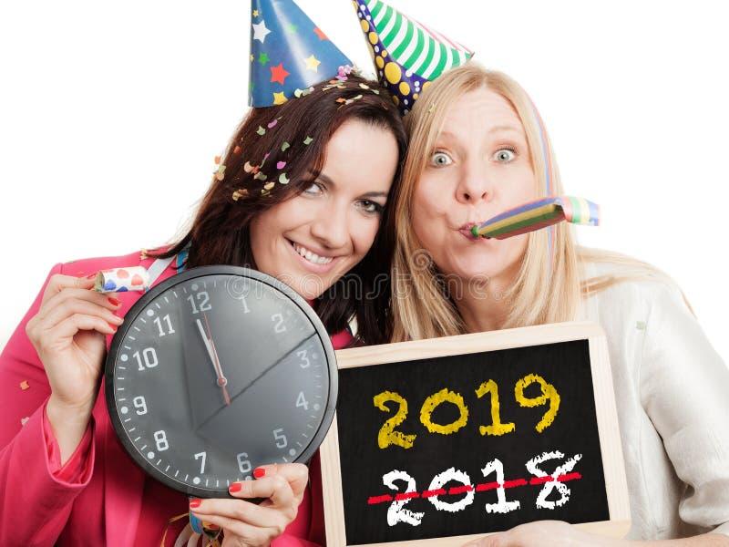 Två kvinnor rymmer den svart tavlan för det nya året 2019 - som isoleras på vit bakgrund royaltyfri fotografi