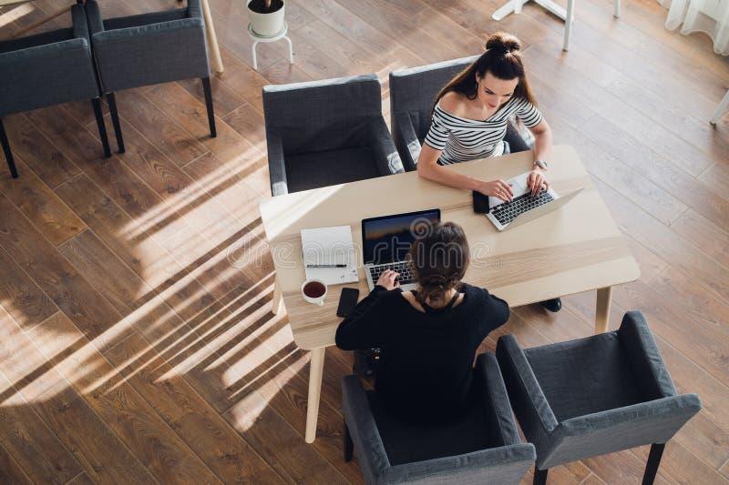 Två kvinnor sitter på tabellen och diskuterar jobbproblem och löser frågor i arbete royaltyfri foto
