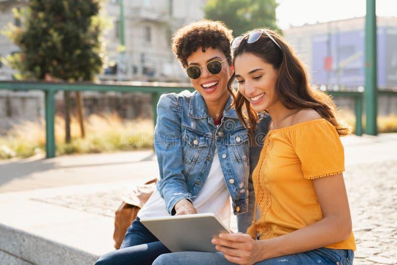 Två kvinnor som använder den utomhus- digitala minnestavlan royaltyfri foto