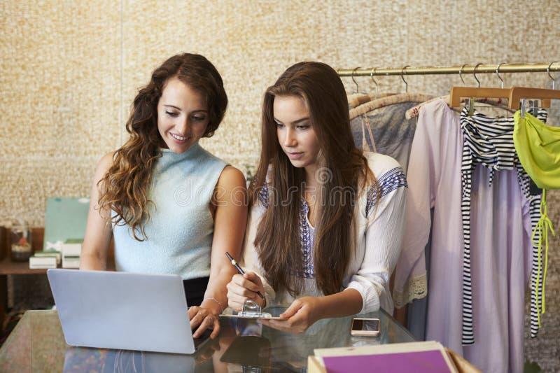 Två kvinnor som arbetar i kläder, shoppar genom att använda en bärbar datordator arkivbild