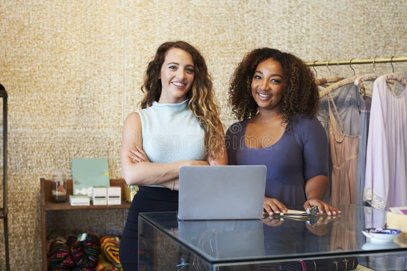 Två kvinnor som arbetar i klädlagret som ser till kameran arkivbild