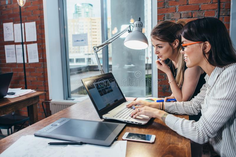 Två kvinnor som arbetar på den nya websitedesignen som väljer bilder genom att använda bärbara datorn som surfar internet royaltyfri bild