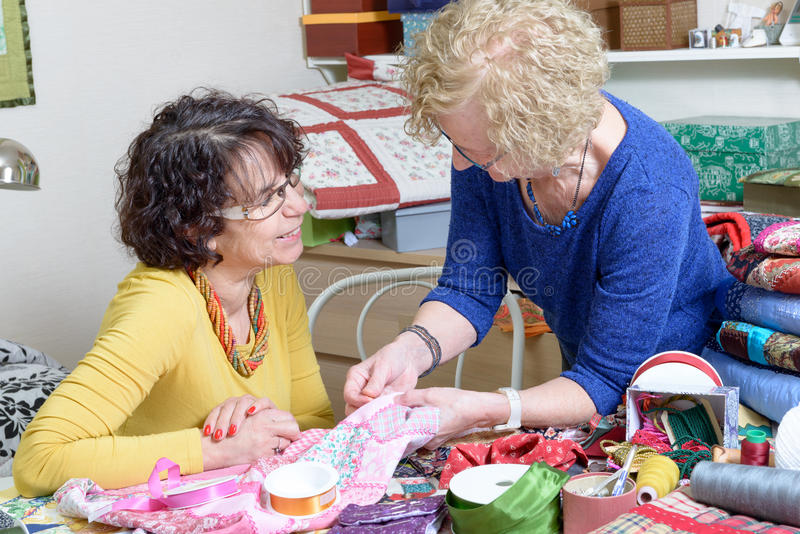 Två kvinnor som arbetar på deras patchwork royaltyfri fotografi