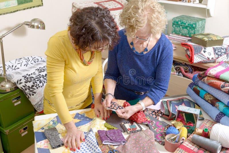 Två kvinnor som arbetar på deras patchwork fotografering för bildbyråer