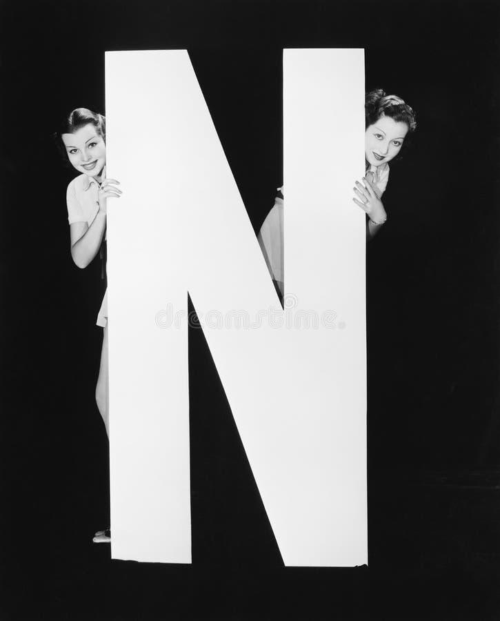 Två kvinnor som döljer bak enorm bokstav N (alla visade personer inte är längre uppehälle, och inget gods finns Leverantörgaranti arkivbilder