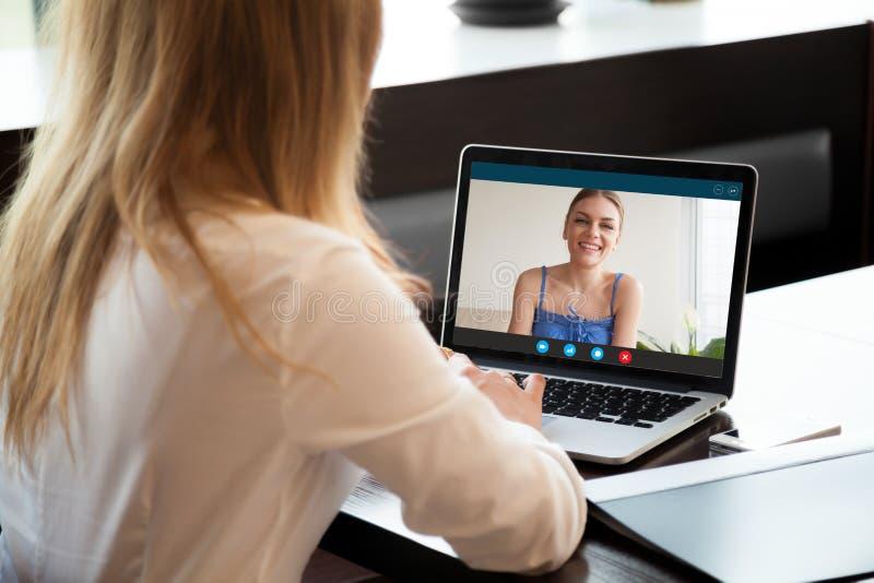 Två kvinnor som direktanslutet pratar, genom att göra den videopd appellen på bärbara datorn royaltyfria bilder