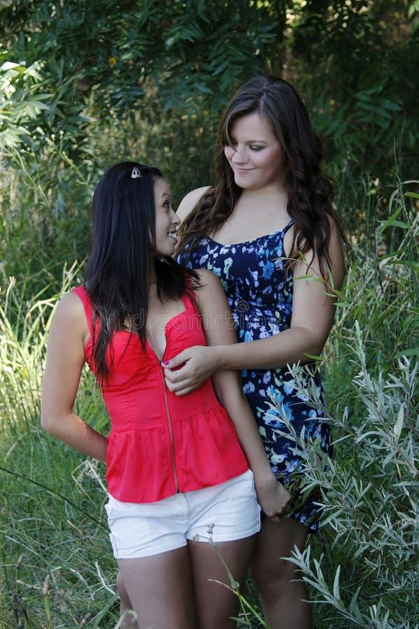 Två kvinnor som drar ned blixtlåset på utomhus den bästa Caucasian asiatet royaltyfria foton