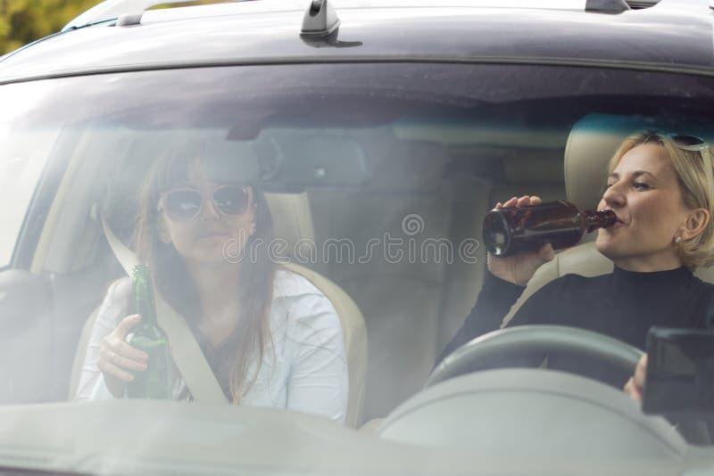 Två kvinnor som dricker, medan köra en bil arkivbilder