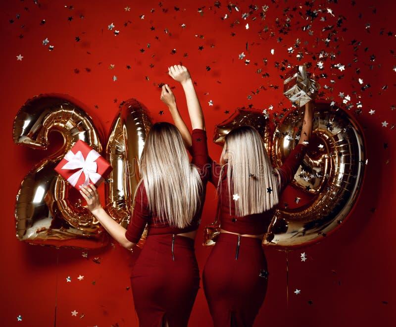 Två kvinnor som firar på flickor för partiet för det nya året lyckliga skratta i tillfälliga klänningar, kastar guld- stjärnakonf royaltyfri foto