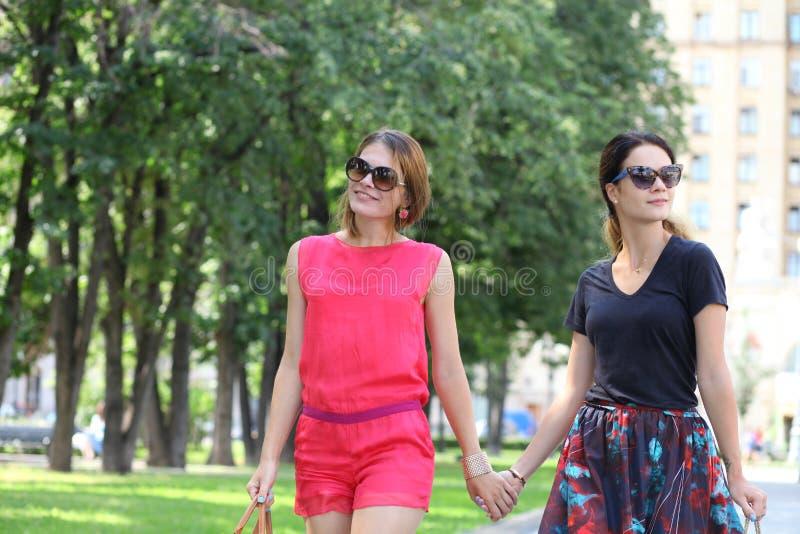 Två kvinnor som går i sommarstaden arkivfoto