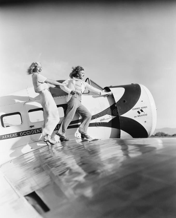 Två kvinnor som går på vingen av en nivå (alla visade personer inte är längre uppehälle, och inget gods finns Leverantörgarantith royaltyfri foto