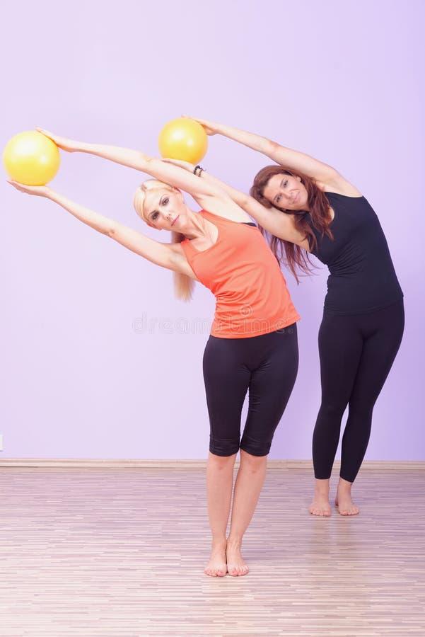 Två kvinnor som gör den Pilates övningen fotografering för bildbyråer