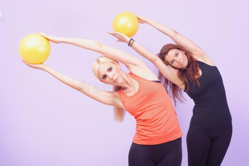 Två kvinnor som gör den Pilates övningen arkivbilder
