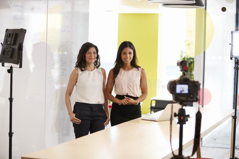 Två kvinnor som gör en företags demonstrationsvideo royaltyfri bild