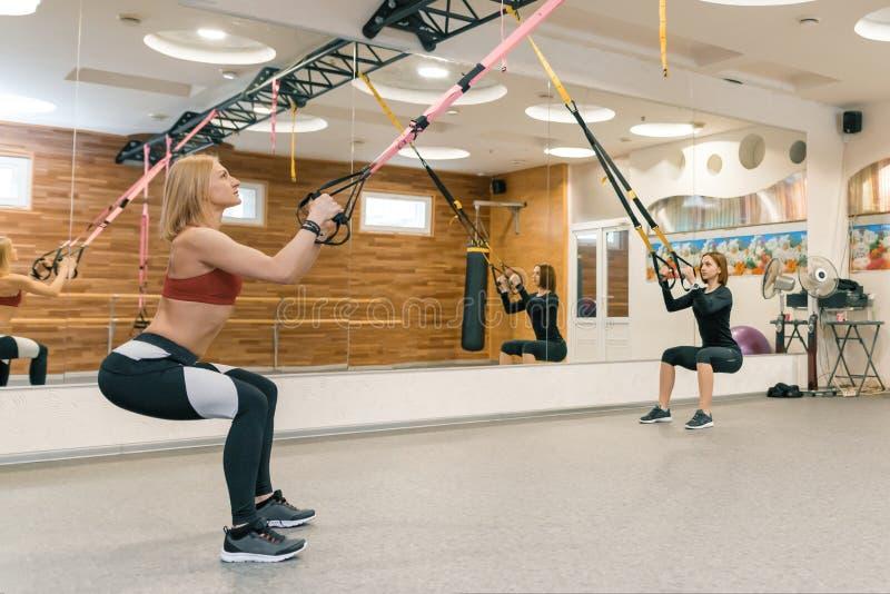 Två kvinnor som gör gruppgenomkörare med konditionremmar i idrottshall Sport kondition, utbildning, sunt livsstilbegrepp arkivfoton