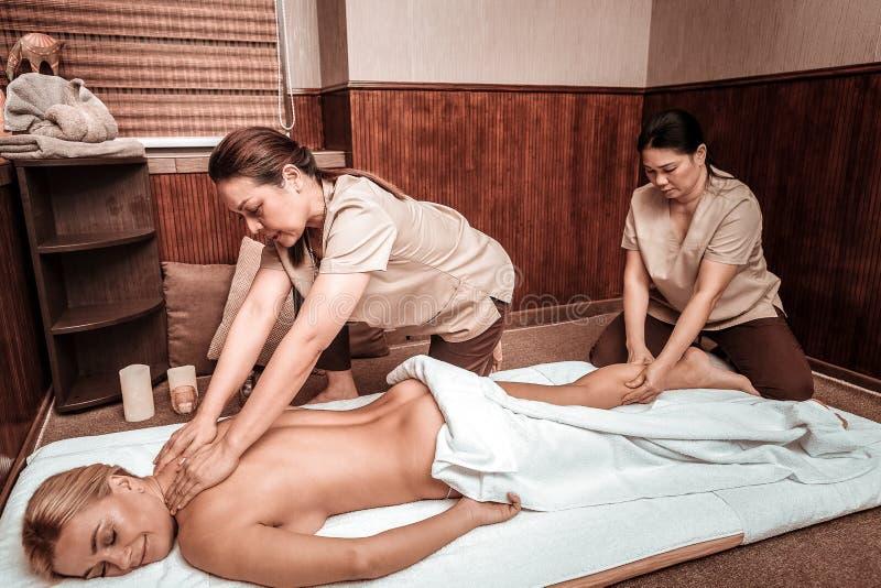 Två kvinnor som gör oljamassage i massagesalong arkivbilder