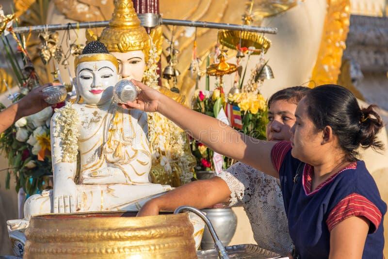 Två kvinnor som häller vatten över Buddhastatyn fotografering för bildbyråer